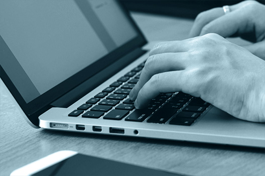 Kunde beim Schreiben eines Tickets am Laptop
