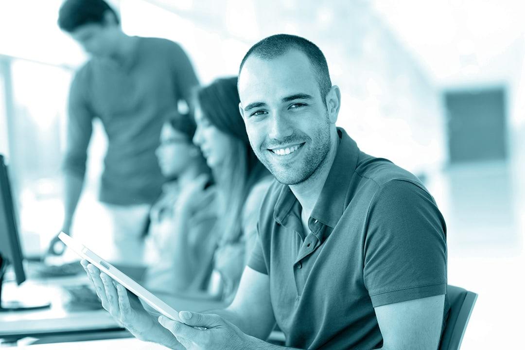 Ein zufrieden lächelnder Teilnehmer eines Software-Trainings, wie es im Rahmen der Shareflex-Schulungen von Portal Systems angeboten wird