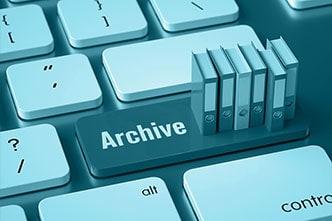 Computer-Tastatur mit Archiv-Taste und Miniatur-Aktenordnern als Symbolbild für die revisionssichere Archivierung.