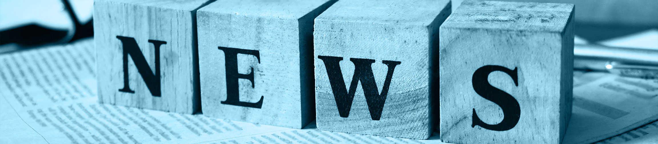 News als Schriftzug auf vier Holzblöcken