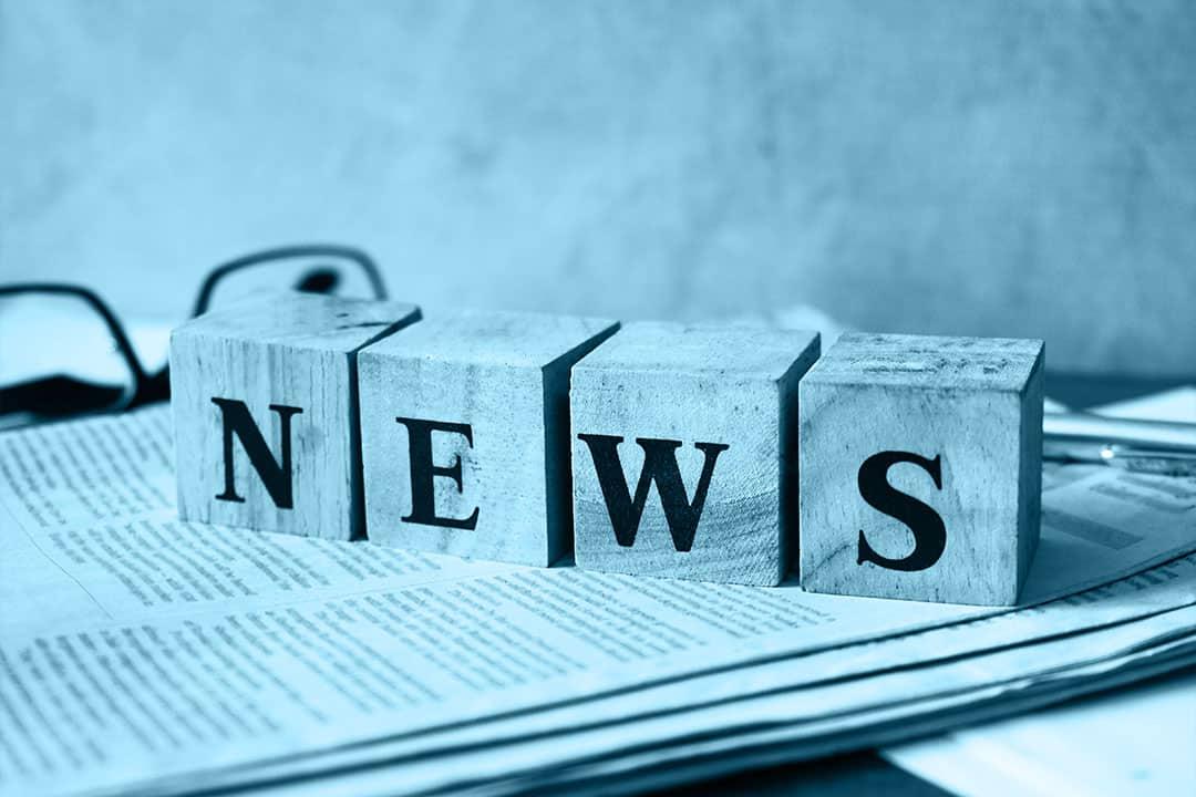 News-Schriftzug auf vier Holzblöcken, die auf einer Zeitung liegen