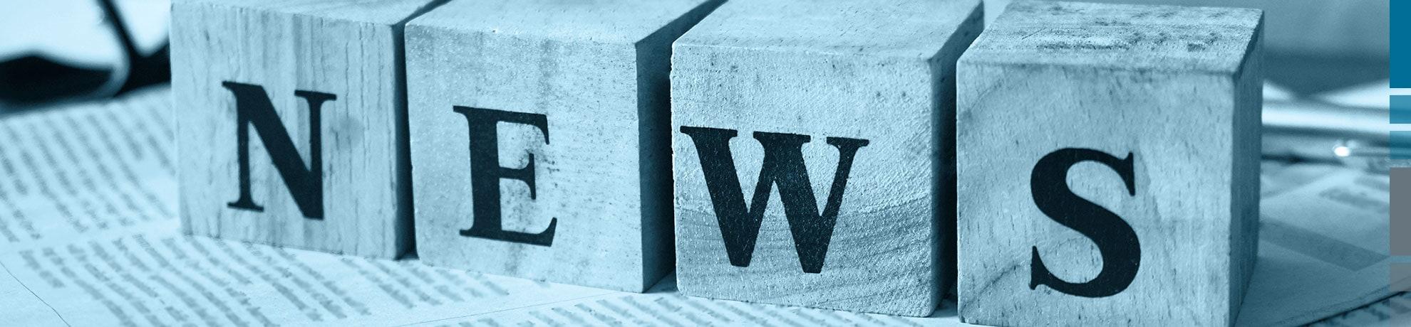 News als Schriftzug auf vier Holzblöcken.