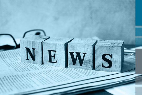 News-Schriftzug auf vier Holzblöcken, die auf einer Zeitung liegen.