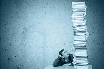 Young man with glasses in front of a huge pile of files